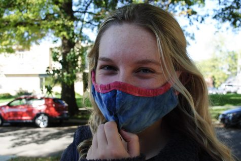 Robin G. giggles as she adjusts her mask for a walk on campus.